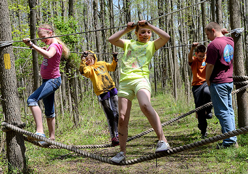 Kids walking along ropes course on forest trail