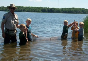 Naturalist and five kids holding a seine net in the water