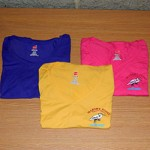 Three v neck shirts, in different colors, with small Marshy Point logo on front