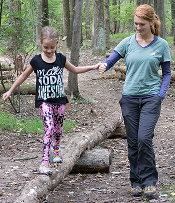 Adult holds girl's hand as she walks over an obstacle in the kid Marsh Mucker course