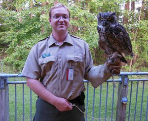 Naturalist Ben Porter with owl on gloved hand