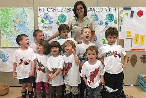Naturalist with kids wearing decorated shirts in preK classroom