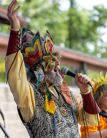 Man in costume talking into microphone with one hand raised