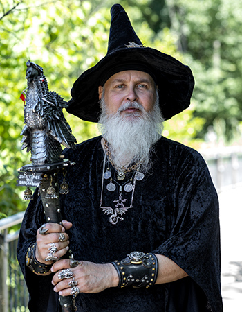 Man dressed in long robe and sorcerer hat with wood and metal dragon staff