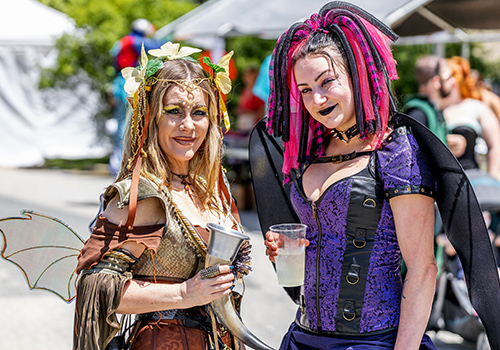 Two women dressed as faeries and holding drinks