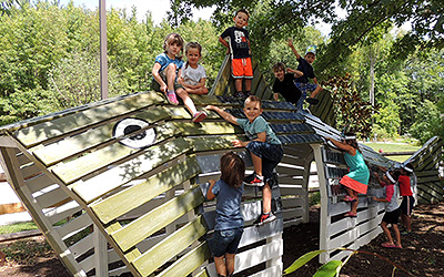Children climbing on wood play set shaped like a fish